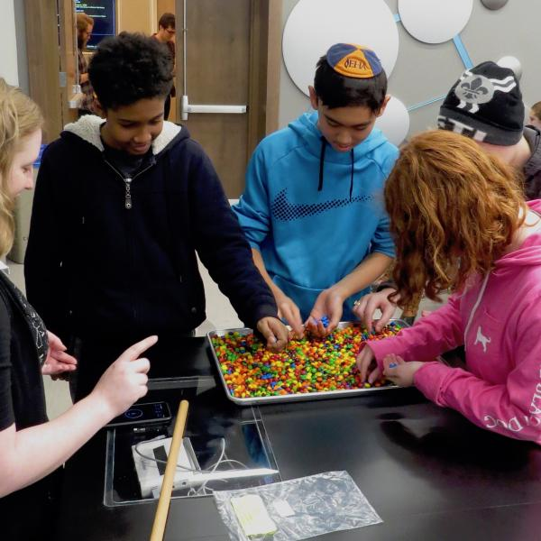 Student participants implement an M&M model of biological evolution as Siera gives pointers